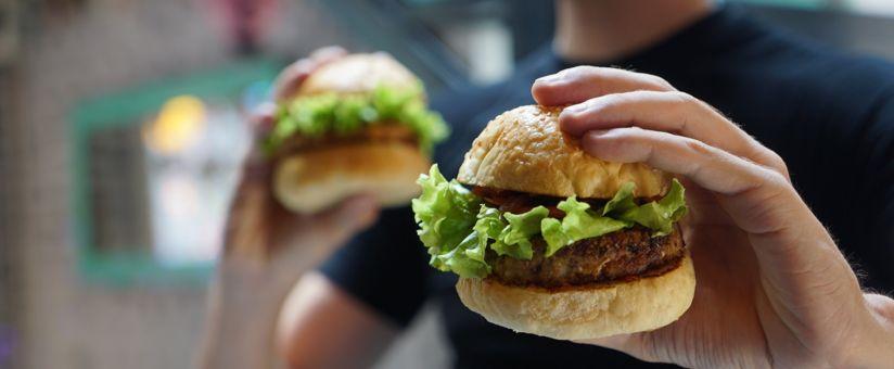 homme-tenant-deux-hamburgers