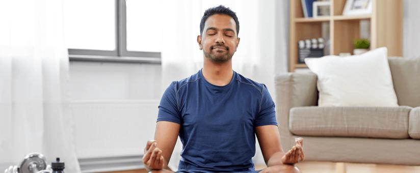 homme-pratiquant-yoga-dans-son-salon